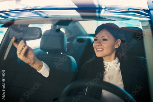 Young woman driver adjusting her rearview mirror in the car.