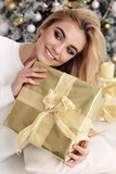 beautiful girl with blond hair in cozy clothes posing near New Year tree with presents - 181161432