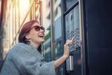 Happy woman using intercom at building entrance. - 181167293