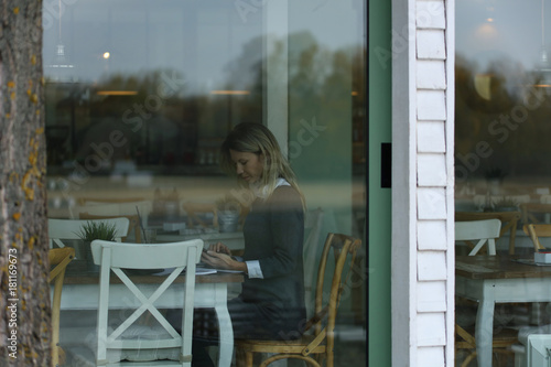 Fototapeta Young woman woking On Lunch Break in cafe,. View through the window.