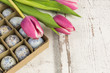 quails eggs in a box with tulips