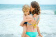 Young mother showing her love to the daughter while standing on the beach