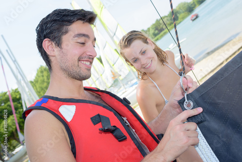 man and woman preparing their boat before sailing
