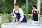 male waiter setting wedding table - 181187280