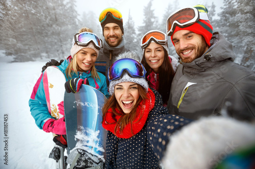 winter, extreme sport and people concept - friends having fun on the snow and making selfie