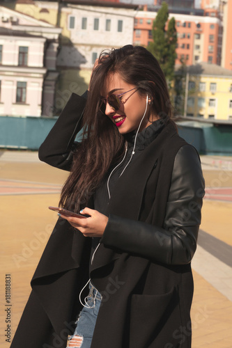 Fotobehang Muziek Pretty smiling brunette woman listen music on mobile telephone, walking at the street