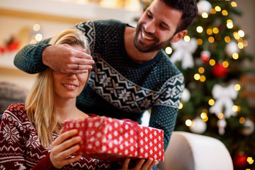 man covering woman's eyes with hands and giving gift box.