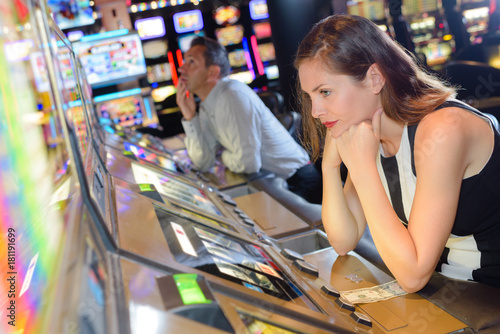 Woman losing on machine in casino Poster