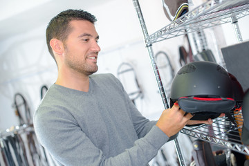 Man looking at horse riding helmet