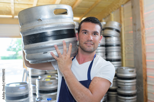 Plakat worker carrying barrel with beer at the brewery