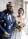 Cheerful Newlywed Couple Throwing Confetti Wedding Ceremony - 181206896