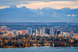 Bellevue Washington. The snowy Alpine Lakes Wilderness mountain peaks rise behind the urban skyline. - 181210213