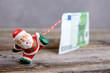 Quadro little Santa Claus pulling big banknote