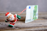 little Santa Claus pulling big banknote - 181216618