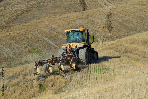 Deurstickers Toscane Crawler tractor with plow on a beveled field