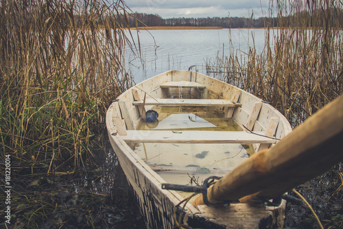 An old flooded boat on the bank of a river or lake in autumn © nikchala