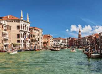 View of the Grand Canal, boats with tourists and the Rialto Bridge. Venice, Italy