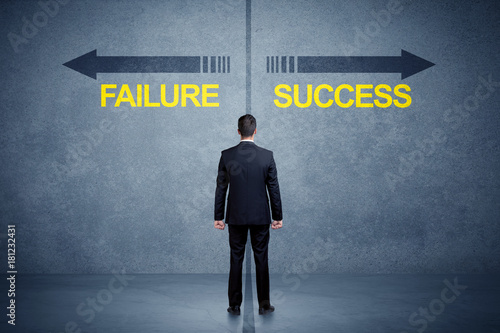 Wall mural Businessman standing in front of success and failure arrow concept