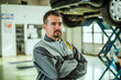 Portrait of a middle aged car worker in his shop.
