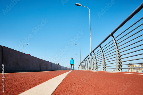 Vast roadway for jogging and cycling with sportsman standing in perspective