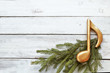 Golden music note on christmas tree branch on wooden background