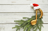 Golden music note with santa hat  on christmas tree branch on wooden background  - 181275085