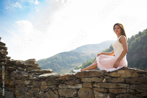 Fototapeta Young woman near a stone wall