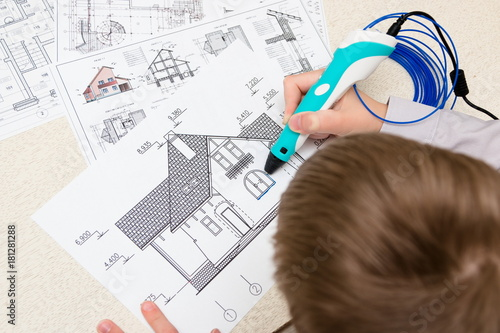 Fototapeta Teenager boy draws a house 3d pen with a blue plastic handle. Architectural plans and drawings. Mathematics. Engineering. Technology. STEM education.