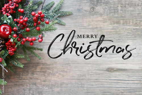 Merry Christmas Text with Christmas Evergreen Branches and Berries in Corner Over Rustic Wooden Background - 181292487