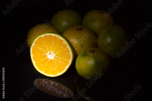 Organic orange and green Mandarin on black background with reflection.