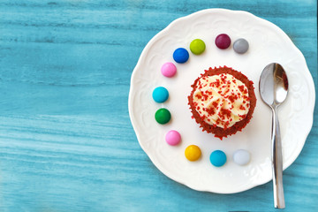 Cupcake with whipped cream and mash cherry from top view, put on the ceramic plate with   colorful chocolate tablets on the blue wooden table