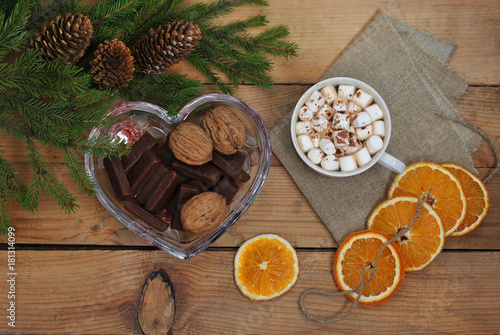 Tuinposter Chocolade Christmas tree branch, coffee, marshmallow, walnuts and chocolate on a wooden table. View from above. Christmas and New Year card. Still life.