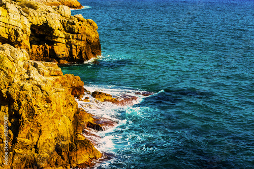 Fotobehang high cliff above the sea, summer sea background, many splashing waves and stone