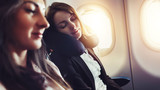 Girlfriends traveling by plane. A female passenger sleeping on neck cushion in airplane.