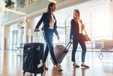 Two stylish female travelers walking with their luggage in airport - 181323444