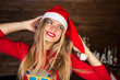 Portrait of attractive girl in Christmas hat in christmas interior. Cheerful and smiling.