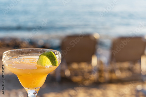 Fotobehang Strand Refreshing Classic Margarita Cocktail With Lime And Salt By The Beach At Sunset On Blurred Background