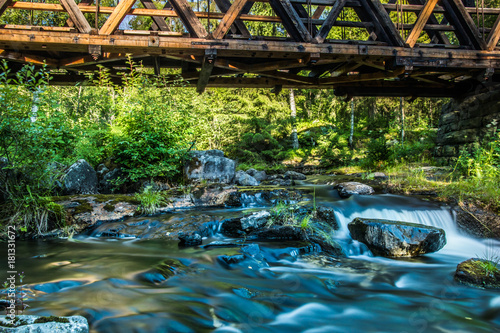 Foto op Canvas Groen blauw A beautiful river with small watefalls and bridge