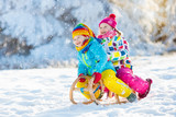Fototapety Kids play in snow. Winter sleigh ride for children