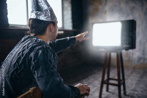 Foto op Canvas UFO Man in aluminum foil helmet reaches out to the TV