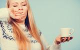 Sleepy woman holding cup of coffee - 181346235