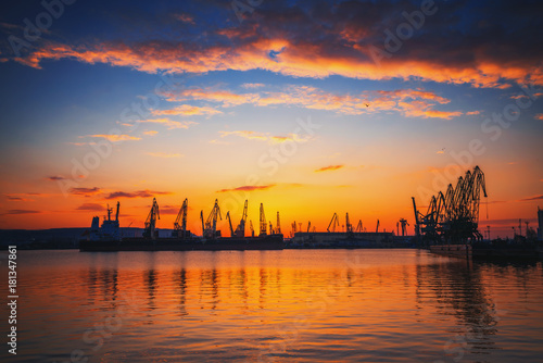 Staande foto Zee zonsondergang Sunset over sea port and industrial cranes, Varna