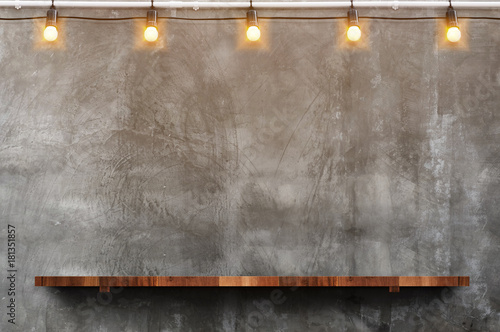 Fototapeta Empty brown wood plank board shelf at grunge concrete wall with light bulb string party background,Mock up for display or montage of product or design