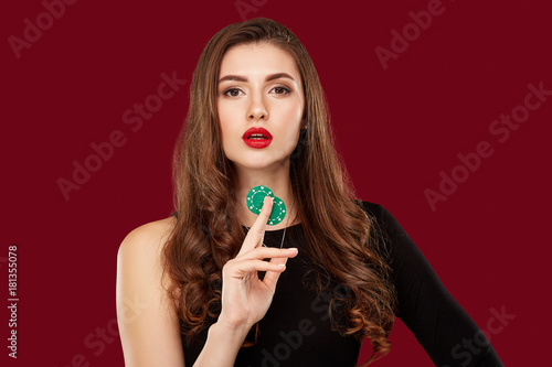 Pretty long hair woman in black dress holding chips for gambling