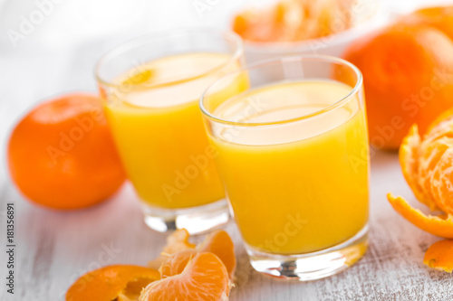 Poster Sap Tangerines, peeled tangerines and tangerine juice in glass. Mandarine juice.