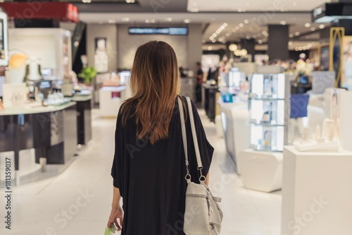 Foto Murales Young asian woman walking in cosmetics department at the mall