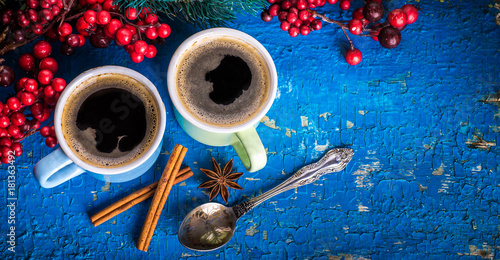 Sticker Cups of fragrant coffee on a Christmas background of fir branches, berries and cones