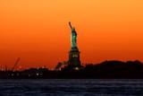 Freiheitsstatue, Sonnenuntergang mit orange gelbem Himmel, New York - 181365697