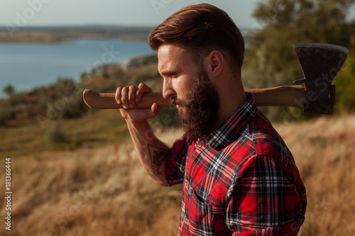 Brutal man with axe on nature