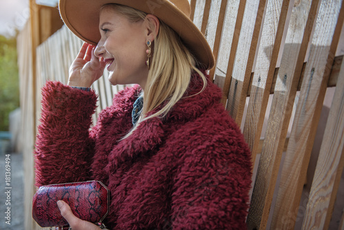 Plakát Side view profile of cheerful young woman covering her eyes from sunshine by hat